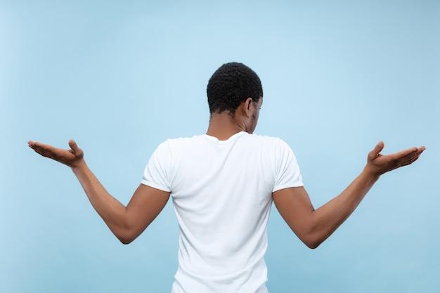 Metade do comprimento fechar o retrato de um jovem afro-americano de camisa branca no espaço azul. emoções humanas, expressão facial, anúncio, conceito de vendas. incerteza, dúvidas