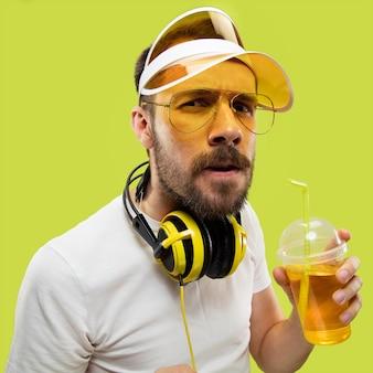 Metade do comprimento fechar o retrato de um jovem de camisa. modelo masculino com fones de ouvido e bebida. as emoções humanas, expressão facial, verão, conceito de fim de semana. ficando sério.