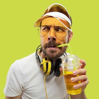 Metade do comprimento fechar o retrato de um jovem de camisa. modelo masculino com fones de ouvido e bebida. as emoções humanas, expressão facial, verão, conceito de fim de semana. perguntando e olhando.