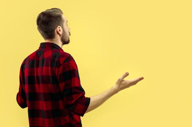 Metade do comprimento fechar o retrato de um jovem de camisa no espaço amarelo. as emoções humanas, o conceito de expressão facial. vista frontal. cores da moda. espaço negativo