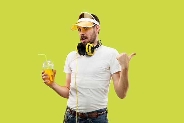 Metade do comprimento fechar o retrato de um jovem de camisa no espaço amarelo. modelo masculino com fones de ouvido e bebida.