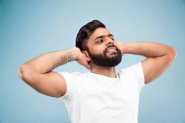 Metade do comprimento fechar o retrato de um jovem hindu de camisa branca na parede azul. emoções humanas, expressão facial, conceito de anúncio. espaço negativo. descansando, relaxando, parecendo calmo.