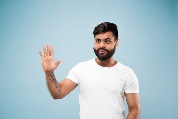 Metade do comprimento fechar o retrato de um jovem hindu de camisa branca na parede azul. emoções humanas, expressão facial, conceito de anúncio. espaço negativo. mostrando a barra de espaço vazia, apontando, saudando.