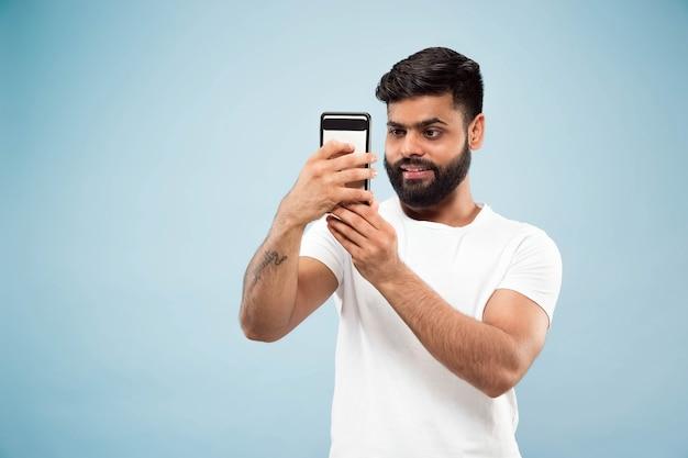 Metade do comprimento fechar o retrato de um jovem hindu de camisa branca sobre fundo azul. emoções humanas, expressão facial, conceito de anúncio. espaço negativo. fazendo selfie ou videoblog, vlog, bate-papo.