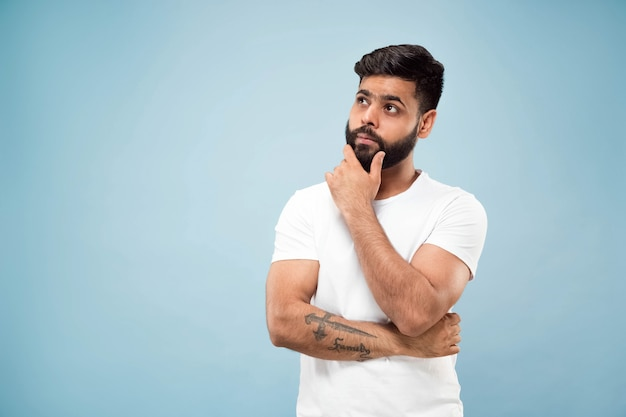 Metade do comprimento fechar o retrato de um jovem hindu em uma camisa branca sobre fundo azul. emoções humanas, expressão facial, conceito de anúncio. espaço negativo. pensando enquanto segura a mão em sua barba. escolhendo.