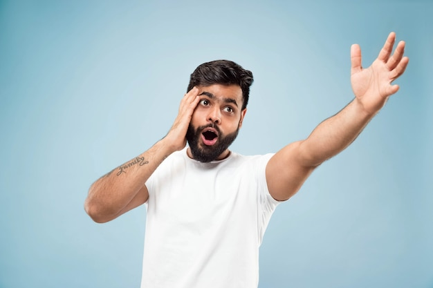 Metade do comprimento fechar o retrato de um jovem hindu em uma camisa branca sobre fundo azul. emoções humanas, expressão facial, vendas, conceito de anúncio. espaço negativo. apontando para ficar chocado e surpreso.