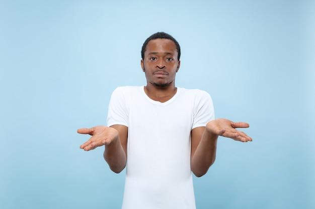 Metade do comprimento fechar o retrato do jovem modelo masculino afro-americano na camisa branca no espaço azul. emoções humanas, expressão facial, conceito de anúncio