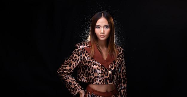 Metade do corpo do retrato de mulher asiática jovem pele bronzeada alta costura usa vestido padrão de pele de cobra. estúdio de iluminação de fundo preto isolado cópia espaço para logotipo de texto, luz retroiluminada com efeito de névoa