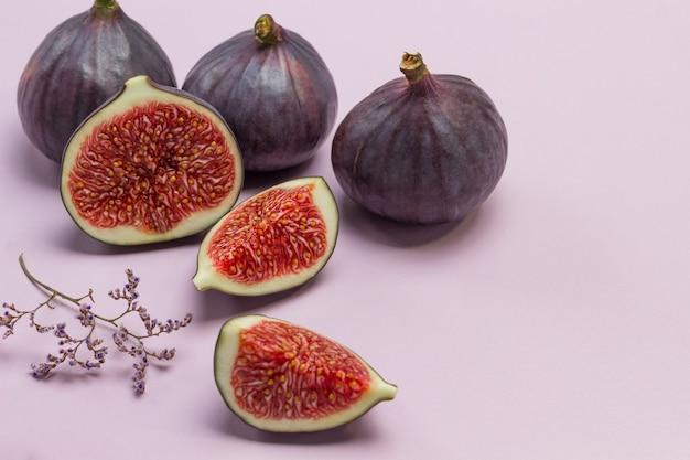 Metade do figo e uma fatia de figo. três figos inteiros. fundo rosa. vista do topo