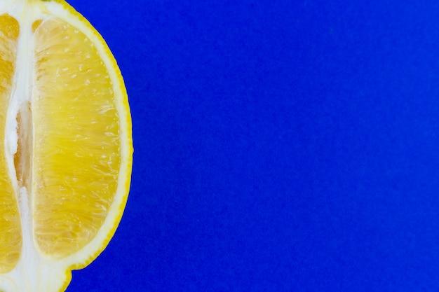 Metade do limão amarelo maduro isolado no fundo azul.