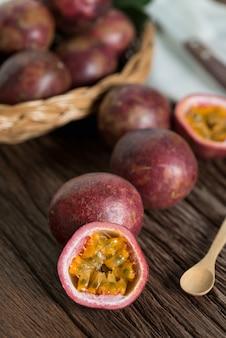 Metade do maracujá e do passionfruit orgânico na cesta de madeira, fundo de madeira.