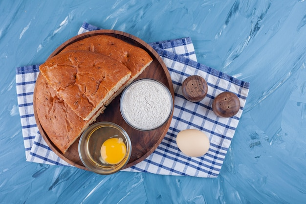 Metade do pão branco fresco com ovo cru e farinha numa toalha de mesa.