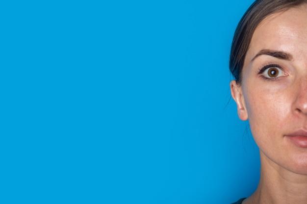 Metade do rosto de jovem em um fundo azul. otoplastia, cirurgia.