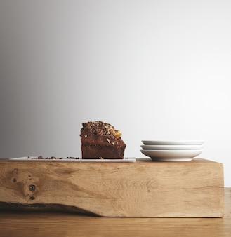Metade do saboroso bolo de chocolate com frutas secas em um prato longo branco perto de três pequenos pratos de chá em branco em um tijolo cru de madeira e uma mesa grossa em um café