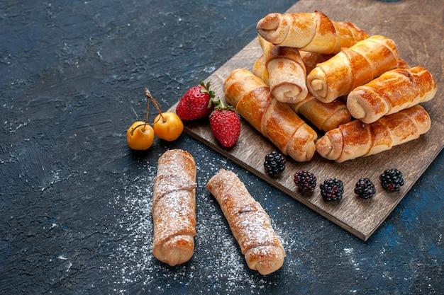 Metade do topo vista de perto deliciosas pulseiras doces com recheio gostoso assadas com frutas na mesa escura, assar bolo biscoito açúcar doce sobremesa