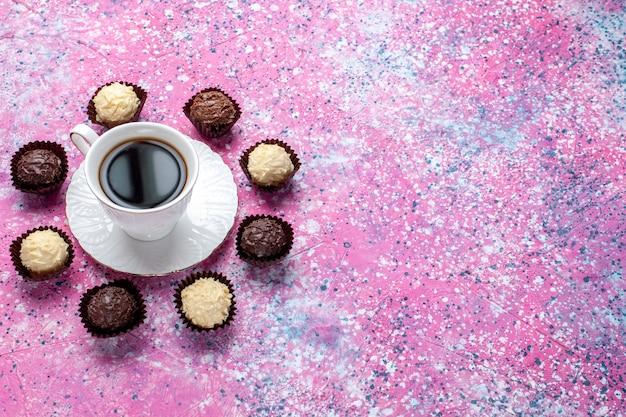 Metade do topo vista deliciosos bombons de chocolate branco e escuro de chocolate com uma xícara de chá no fundo rosa.