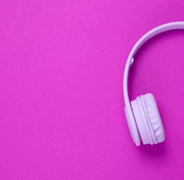 Metade dos fones de ouvido roxos em fundo rosa
