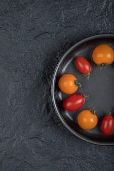 Metade dos tomates cereja coloridos na panela em fundo preto. foto de alta qualidade