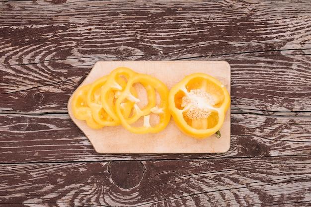 Metade e fatias de pimentão amarelo na tábua sobre o pano de fundo de textura de madeira