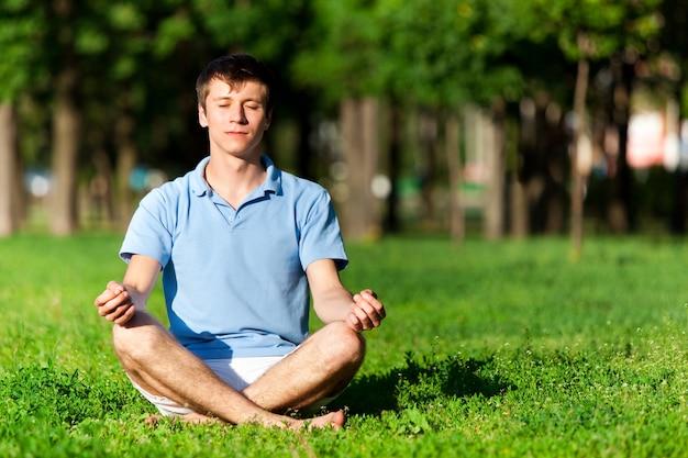Metade homem nu, sentado na grama verde, meditando e fazendo pose de ioga