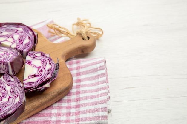Metade inferior da vista repolho roxo picado em uma tábua em uma toalha de cozinha quadriculada rosa e branca em uma mesa cinza com espaço livre