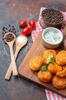 Metade inferior vista bolas de queijo na tábua de madeira com molho de tomate cereja colheres de pau pimenta preta em fundo escuro