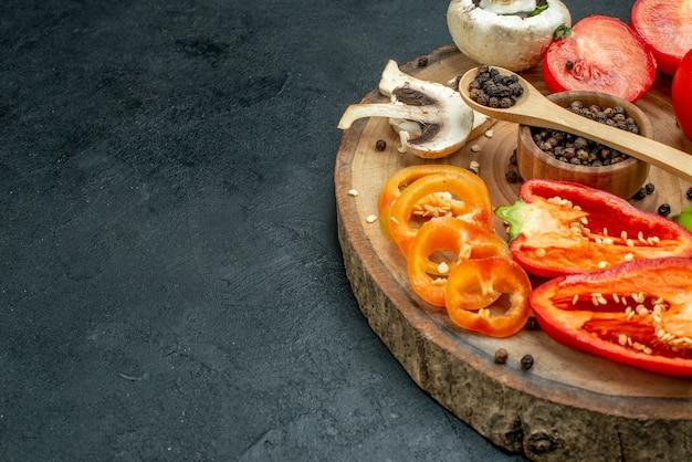 Metade inferior vista legumes frescos cogumelos pimenta preta em uma tigela colher de pau tomates vermelhos pimentões na placa de madeira na mesa escura com espaço livre