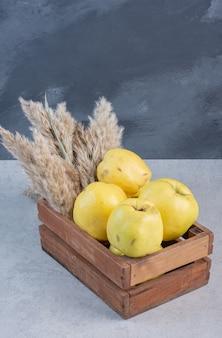 Metade orgânica madura fresca e marmelos inteiros em cesta de madeira.