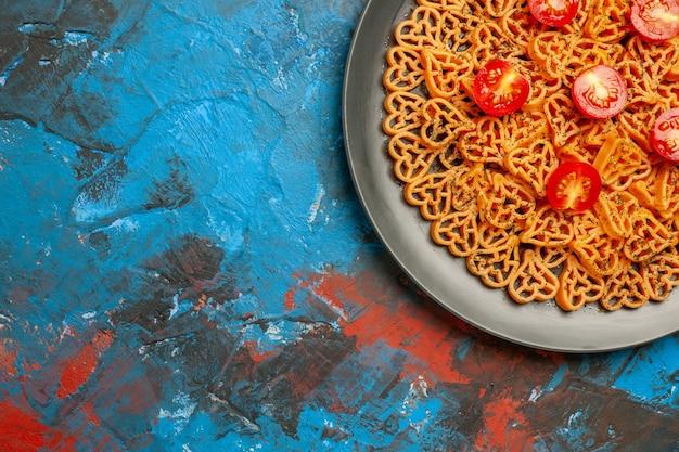 Metade superior da vista de corações de massa italiana corta tomates cereja em uma placa oval preta na mesa azul
