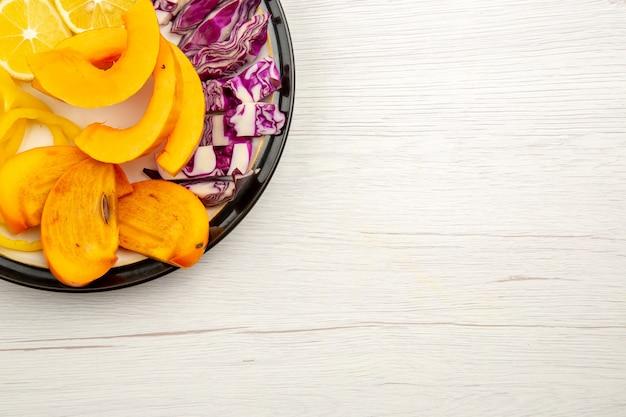 Metade superior da vista de legumes e frutas picados, pimentões de abóbora, caqui, repolho roxo, em placa preta na superfície branca com local de cópia