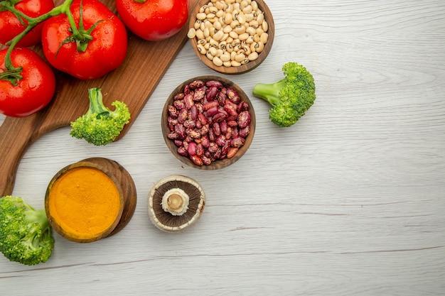 Metade superior da vista do ramo de tomate na tábua de cortar cogumelos, brócolis, feijão, cúrcuma na mesa, espaço livre Foto gratuita