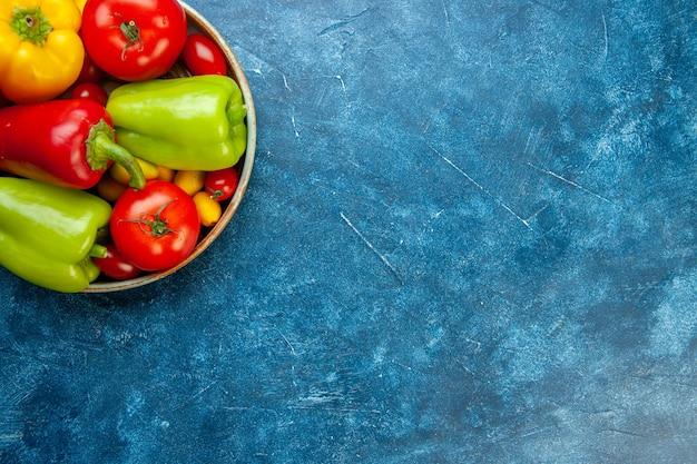 Metade superior da vista legumes tomates cereja cores diferentes pimentões tomates em uma tigela na mesa azul com lugar livre