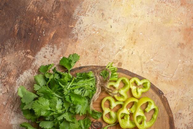 Metade superior veja diferentes vegetais, coentros, pimentões cortados em pedaços em uma placa redonda de madeira com fundo âmbar