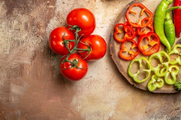 Metade superior ver vegetais diferentes pimentas picantes pimentões cortados em pedaços na tábua redonda de madeira de tomates em fundo amarelo ocre