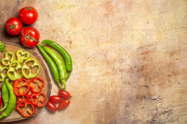 Metade superior, ver vegetais diferentes, pimentas picantes, pimentões cortados em pedaços na tábua redonda de madeira, tomates cereja sobre fundo amarelo ocre