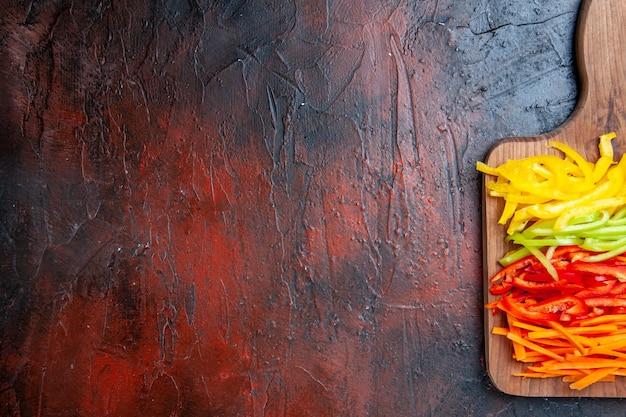 Metade superior vista colorida de pimentas cortadas em uma tábua na mesa vermelha escura com espaço de cópia