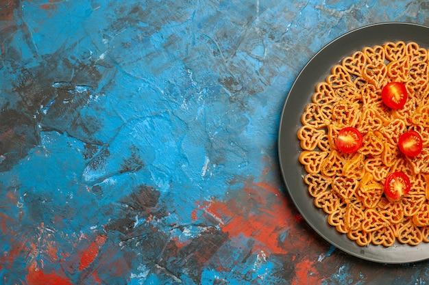 Metade superior vista de corações de massas italianas cortadas tomates cereja