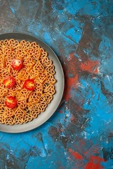 Metade superior vista de corações de massas italianas cortam tomates cereja em um prato oval preto