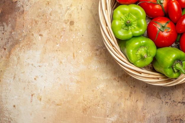 Metade superior vista de tomates de pimentão verde e vermelho em uma cesta de vime em fundo âmbar