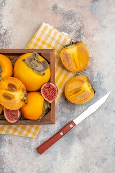 Metade superior vista deliciosos caquis e figos cortados em caixa de madeira um corte caqui uma faca no fundo nu