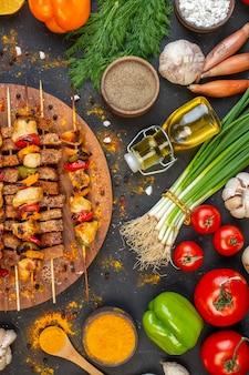 Metade superior vista deliciosos espetos de frango na tábua de madeira e outros alimentos na mesa