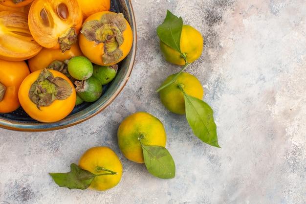 Metade superior vista feykhoas de caquis frescos em uma tigela e tangerinas em um fundo nu