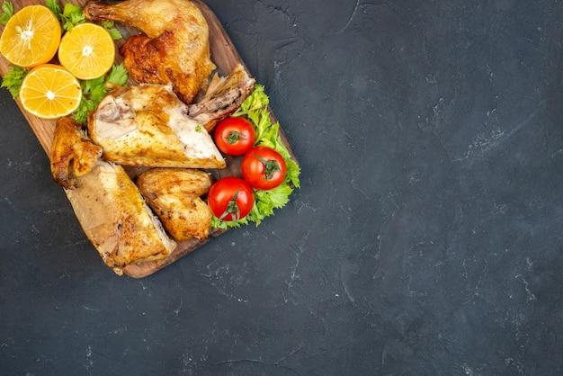 Metade superior vista frango assado, tomate, fatias de limão na placa de madeira no preto