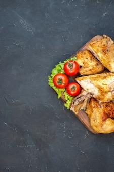Metade superior vista frango assado tomate rodelas de limão na placa de madeira na mesa preta