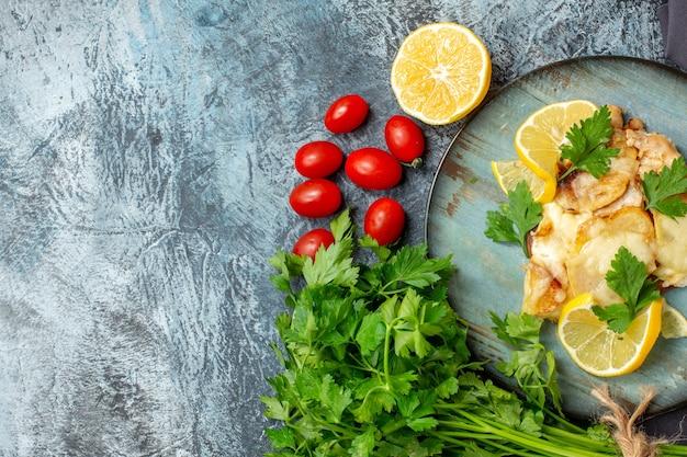 Metade superior vista frango com queijo no prato molho de salsa metade tomate cereja com limão no local de cópia da mesa cinza