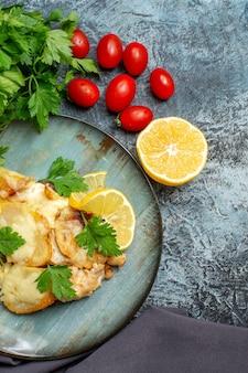 Metade superior vista frango com queijo no prato salsa metade tomate cereja limão na mesa cinza