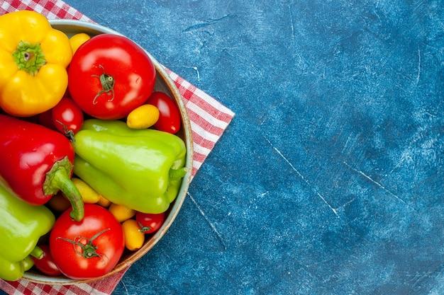 Metade superior vista legumes frescos tomates cereja cores diferentes pimentões tomates cumcuat na bandeja na toalha de mesa quadriculada vermelha e branca na mesa azul com espaço livre