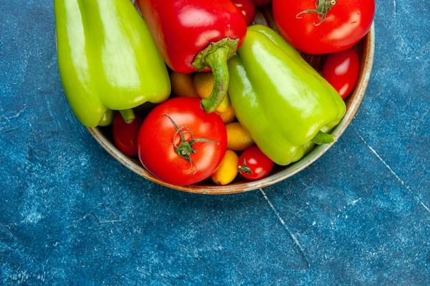 Metade superior vista legumes tomate cereja cores diferentes tomates pimentões em uma tigela na mesa azul