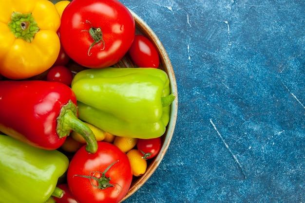 Metade superior vista legumes tomates cereja cores diferentes tomates pimentões em uma bandeja de madeira no lugar da cópia da mesa azul