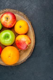 Metade superior vista maçãs limão laranjas na placa de madeira na superfície escura